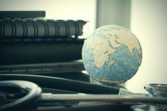 Studio macro of a stethoscope and texture globe Royalty Free Stock Photos