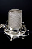 Studio Microphone. A photograph of a condenser studio microphone being held in a shock mount. The image is isolated on a black background Stock Photos