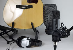 The studio microphone against the background of musical instruments. The professional microphone against the background of a guitar and earphones Stock Photography