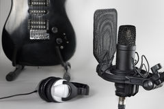 The studio microphone against the background of musical instruments. The professional microphone against the background of a guitar and earphones Stock Photo