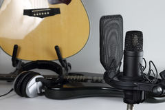 The studio microphone against the background of musical instruments. The professional microphone against the background of a guitar and earphones Royalty Free Stock Photo