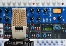 Studio microphone and audio devices. Professional studio microphone and a rack of audio devices, with shallow focus stock image