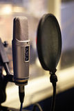 Studio microphone in backlight. Microphone in small broadcastion station Stock Image