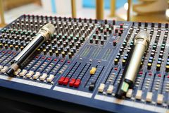 Studio microphone and editing suite. Electronics, communication. Modern studio microphone,Radio studio detail: microphone and mixer Stock Photos
