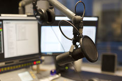 Studio microphone in front of radio station broadcasting equipment. Studio microphone in front of a sound mixer and computers in broadcasting radio studio. New royalty free stock images