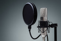 Studio microphone. And pop shield on mic stand against gray background royalty free stock image