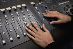 Studio mixing desk. Detail of a mixing desk and sound engineer in a recording studio Royalty Free Stock Images
