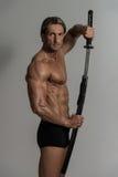 In Studio With modelo masculino musculoso una espada Fotografía de archivo libre de regalías