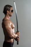 In Studio With modelo masculino musculoso una espada Fotos de archivo
