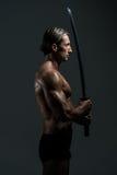 In Studio With modelo masculino musculoso una espada Foto de archivo libre de regalías