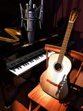 Studio music. A studio microphone  the foreground of a classic guitar on a wooden chair and a great piano Royalty Free Stock Photo