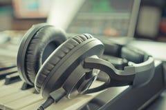 Studio Music headphone on music keyboard in a Home music studio DAW. Desktop stock image