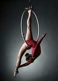 Studio photo of acrobatic girl dancing with hoop. On grey background Royalty Free Stock Photo
