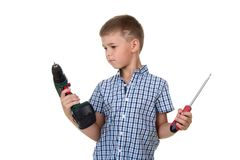 Studio photo of a cute kid in blue checkered shirt, holding instrumnts and trying to choose a screwdriver. Isolated on white background Royalty Free Stock Image