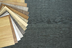 A studio photo of sample laminate flooring wood texture floor. S. Color palette for furniture on table close-up.Samples of laminate and vinyl floor tile on Royalty Free Stock Images