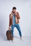 Studio photo of the young man with a travel bag stock image