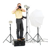 Studio photographer. A professional photographer standing on a flight case to get a higher angle in a studio, surrounded by three strobes Stock Photos