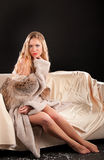 Studio photography. Naked girl wrapped in the fur coat, studio shooting Royalty Free Stock Photo