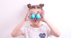 Studio photography: a little girl makes faces with painted Easter eggs. stock images