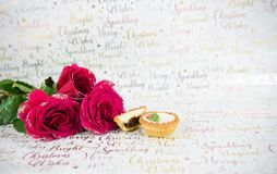 Christmas photography food image of red roses with glitter petals and mince pies on xmas wrapping paper background Stock Image