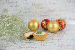 Christmas food photography of flowers with glitter mince pies baubles on xmas wrapping paper background Stock Photos