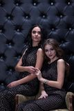Studio photography.Two beautiful girls with dark hair on a black background with rhinestones. stock image