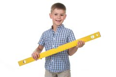 Studio picture of a cute builder boy in a blue checkered shirt, holding a big yellow construction ruler. Studio picture of a cute builder boy in a blue Stock Photos