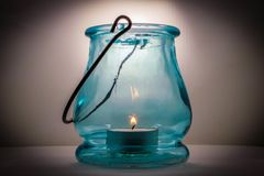 Studio picture of light blue glass lantern with lit candle. A light blue glass lantern with a tea candle lit inside Stock Photography