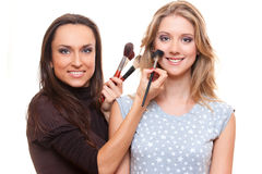 Studio picture of smiley make up artist and client Royalty Free Stock Photos