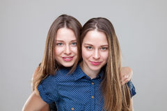 Studio portait of young twin sisters embracing Royalty Free Stock Images