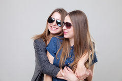 Studio portait of young twin sisters embracing Stock Image
