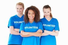 Studio-Porträt von drei Frauen, die freiwillige T-Shirts tragen Stockfotos