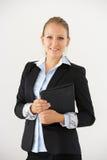 Studio-Porträt von Geschäftsfrau-Standing Against White-Hintergrund, der Digital-Tablet hält Lizenzfreie Stockbilder