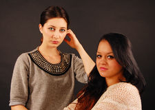 Studio portrait. Of two young beautiful women over the gray background Royalty Free Stock Photos