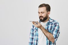 Studio portrait of adult bearded male model holding smartphone near mouth while speaking in it with puzzled expression Royalty Free Stock Photos
