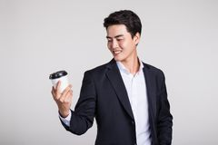 Studio portrait of an Asian business man posing with a disposable coffee cup Royalty Free Stock Images