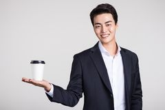 Studio portrait of an Asian business man posing with a disposable coffee cup Stock Photos