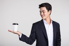 Studio portrait of an Asian business man posing with a disposable coffee cup Royalty Free Stock Image