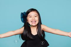 Studio portrait of asian girl with soap bubbles in front of blue background Royalty Free Stock Image