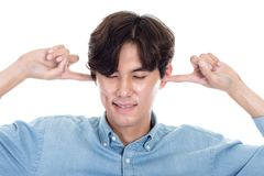 Studio portrait of Asian man blocking ears. Shot Stock Images