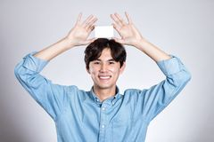 Studio portrait of an asian man holding a card. Shot Royalty Free Stock Image