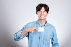 Studio portrait of an asian man holding a card. Shot Royalty Free Stock Photos