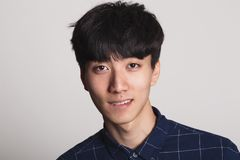 A studio portrait of an Asian young man smiling with a bright smile Royalty Free Stock Images