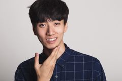 A studio portrait of an Asian young man smiling with a bright smile Royalty Free Stock Image
