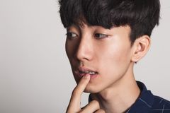 A studio portrait of an Asian young man who is troubled and deep in thought stock images