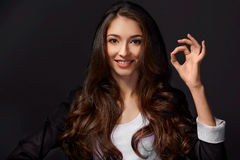 Studio portrait of an attractive woman giving the OK sign to the camera. Studio shot of an attractive young businesswoman Stock Photography