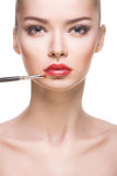 Portrait of woman with lips-brush Royalty Free Stock Photography
