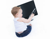 Studio portrait of a baby boy holding a tv remote Royalty Free Stock Image