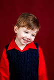 Studio Portrait of a Bashful Boy on Red. An in studio portrait of a shy boy on a deep red backdrop. He is wearing a dark blue sweater vest over a red, collared Royalty Free Stock Photos