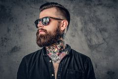 A man with tatoos on his arms. Studio portrait of a bearded hipster man with tattoos on his arms and neck  dressed in a black shirt and sunglasses Royalty Free Stock Photo